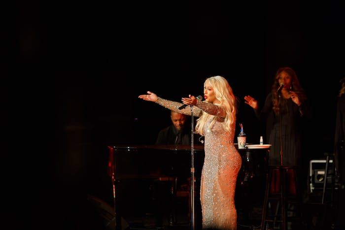 Christina Aguilera sings on stage with her arms outreached