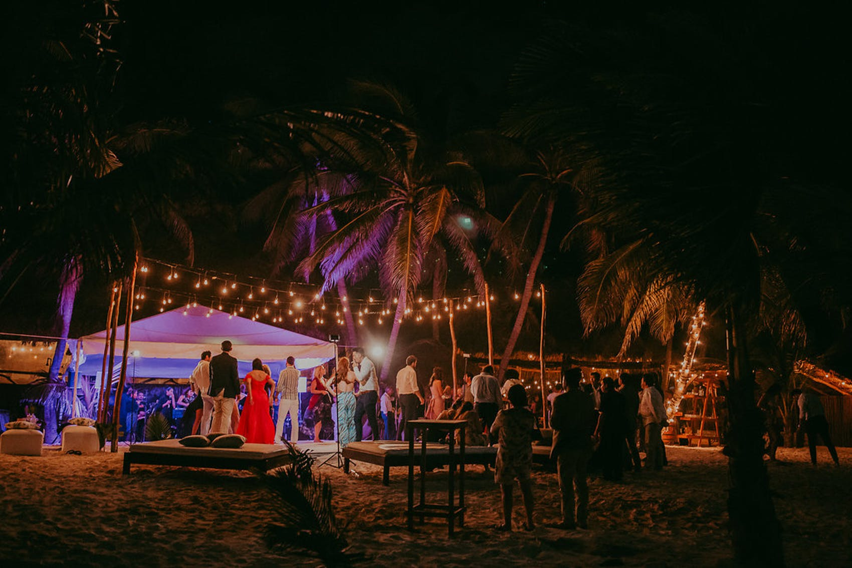 A breezy beach scene. Fairy lights line the perimeter of the dance floor. A white tent is in the background and palm trees are everywhere