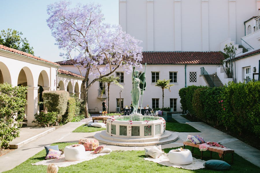 a sparse pink tree and a patinated statue fountain are in the middle ground. Green grass and archways are in the confines of the courtyard.