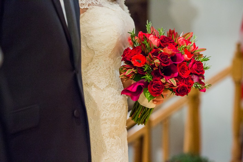 Striking red and fuchsia lilies, ranunculus, and roses for an autumn bouquet.