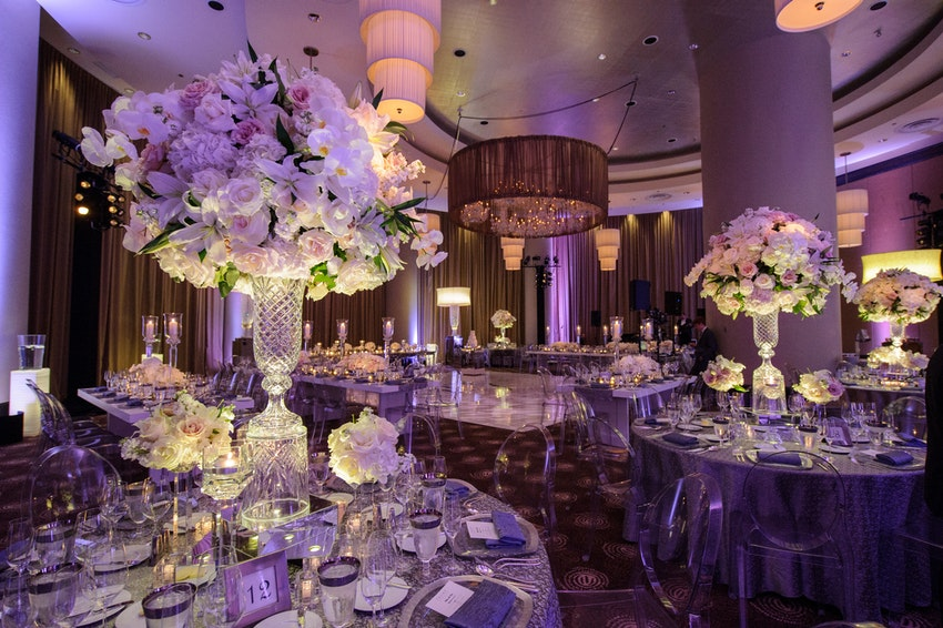 Tall, lush ivory and blush centerpieces in crystal vases for a modern Trump Chicago wedding reception.