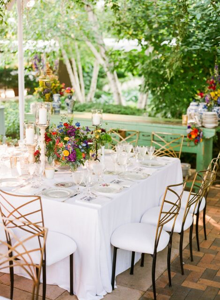 White vibrant linens allow these colorful summer flowers to really pop  throughout the tented reception.