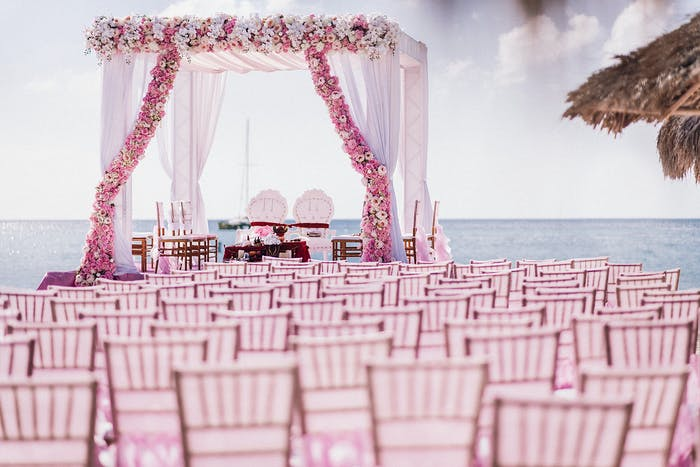 An all pink wedding with pink chairs and a pink archway.