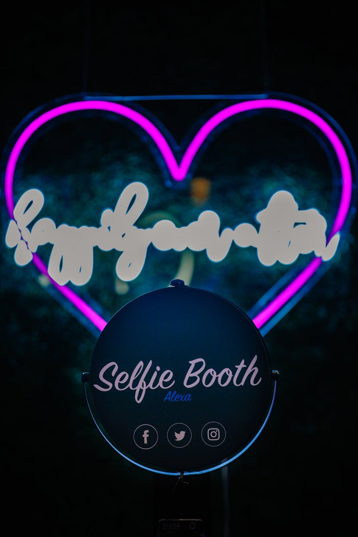 a neon heart advertising a selfie booth