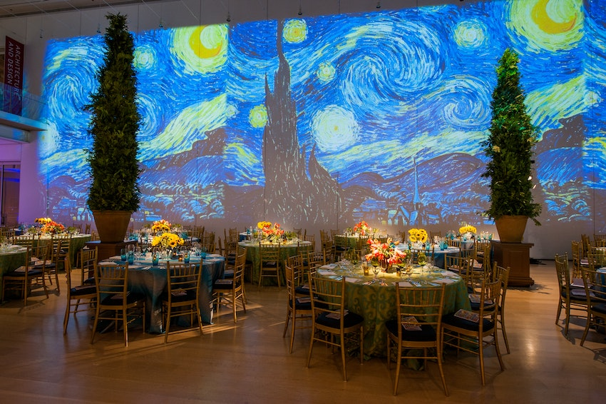Van Gogh Gala at the Art Institute Chicago featuring projections of the artist's paintings on the walls and arborvitae trees.