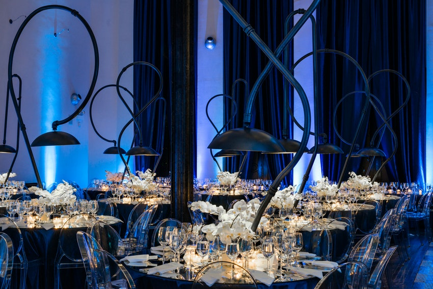 Custom made lamps serve as striking centerpieces along with white phalaenopsis orchids atop mirrored round tables.
