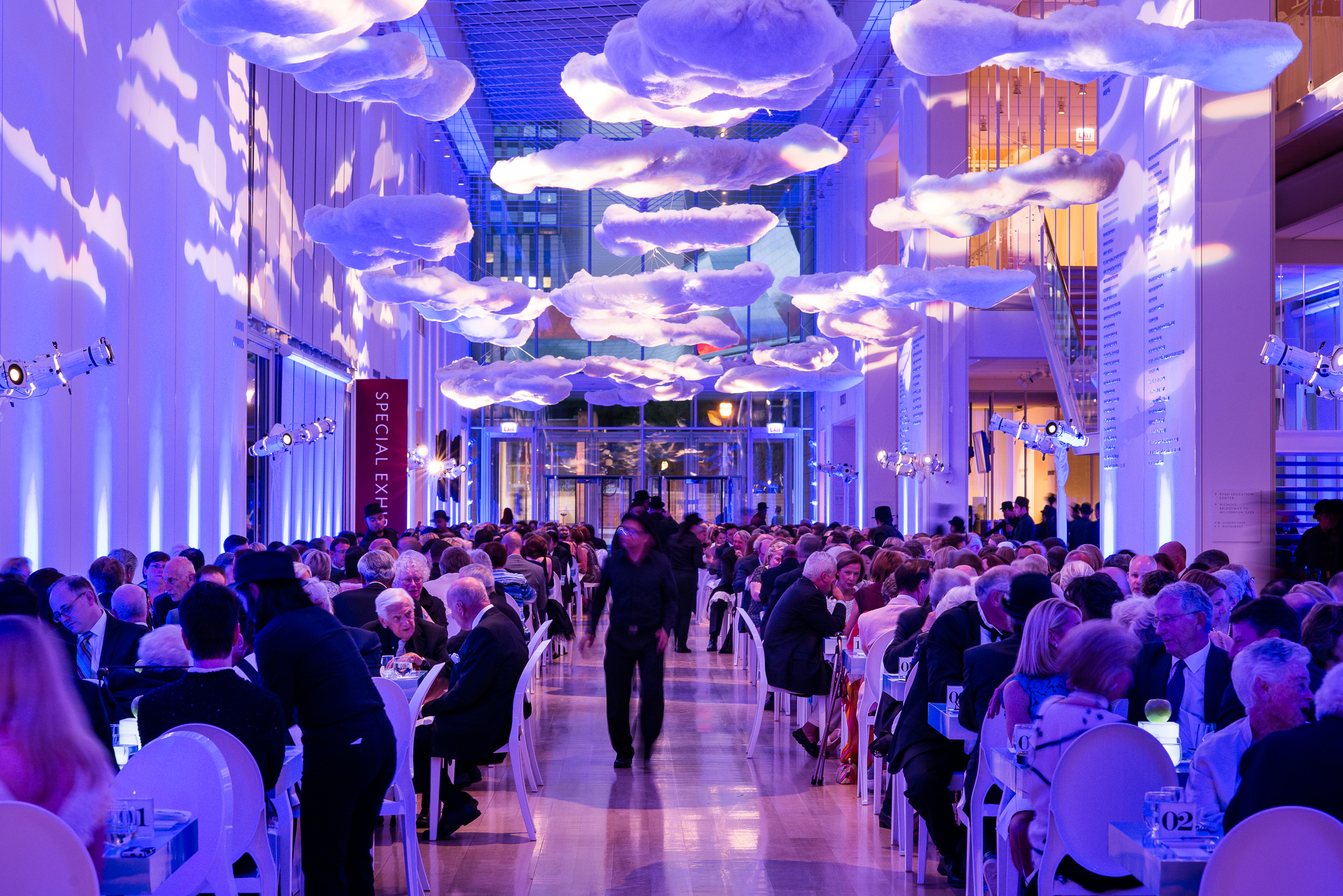Clouds hang from the ceiling and cover the tabletops at the whimsical gala for the Magritte Opening gala at the Art Institute.