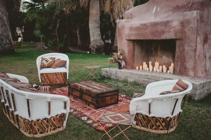 A large sandstone fireplace outside with southwestern themed lounge area and rug in front.