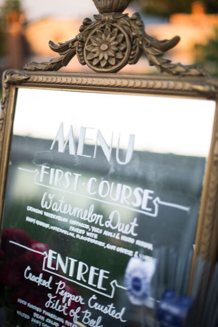 Mirrored menu sign with custom calligraphy lettering.