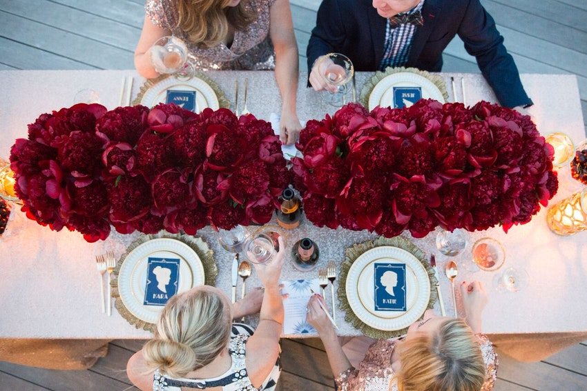 Stunning table decor with a peony centerpiece and gold chargers.