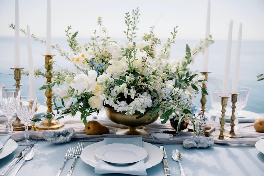 Tablescape with sky blue natural linen, hand-died silk table runner, vintage tabletop elements and distressed white folding chairs with lake backdrop.