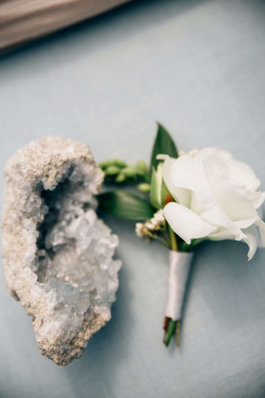 A boutonneire wrapped in white satin ribbon and celestite crystal cluster geode.