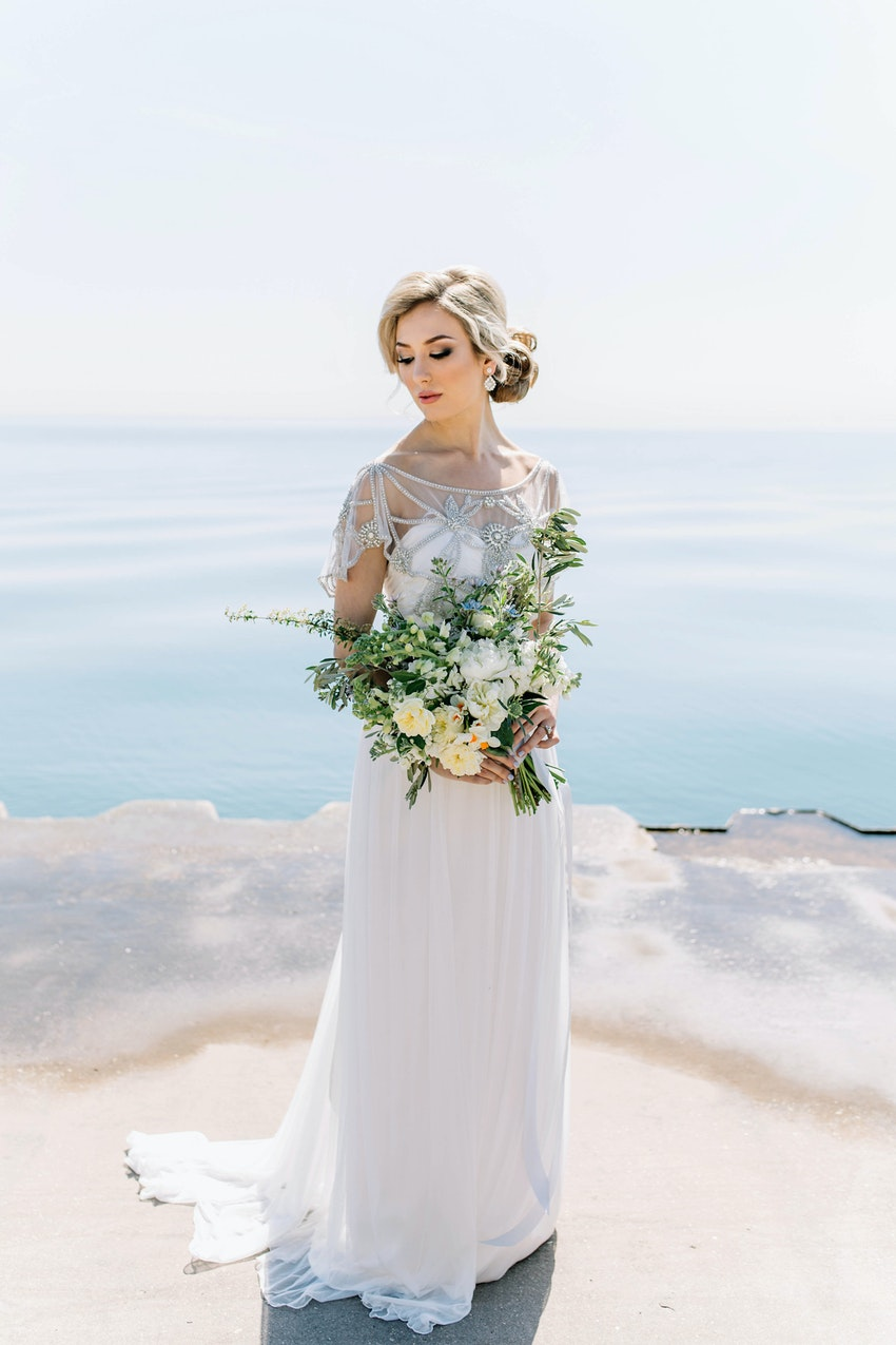 Bride in vintage-inspired dress embellished in crystals holding a natural bouquet at lakefront.