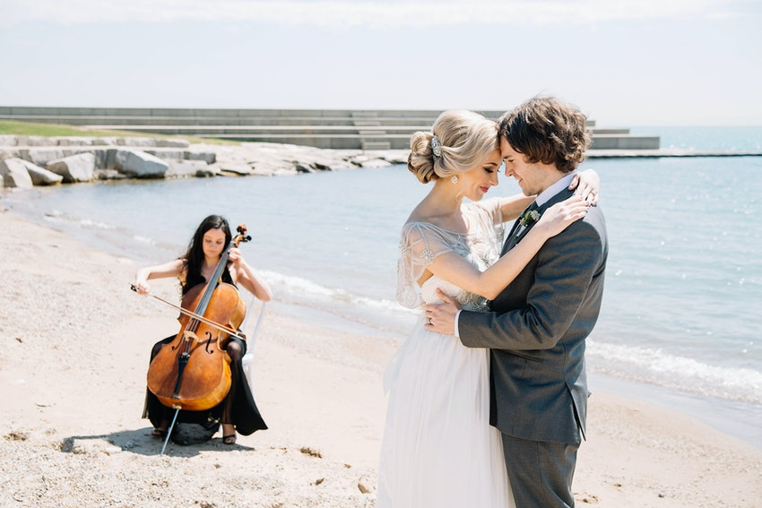 Wedding couple dancing on the beach and cellist.