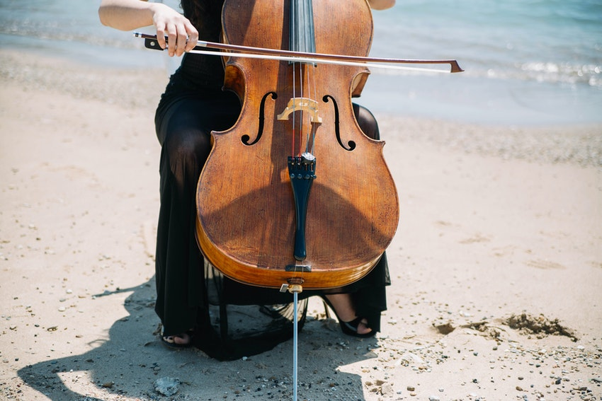 Cellist on the beach/sand.