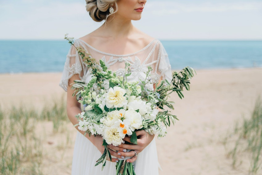 Bride in a vintage-inspired dress holding bouquet.