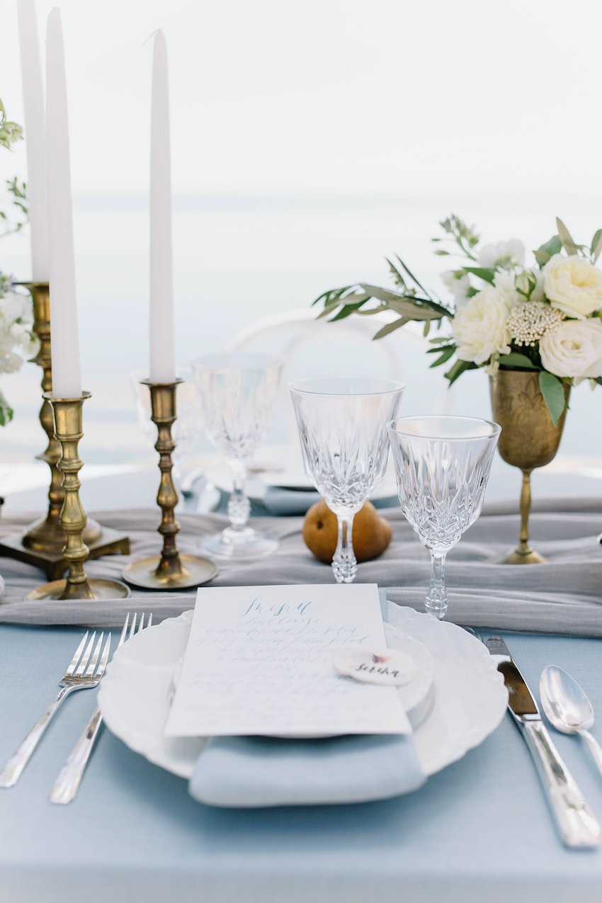 Tablescape with sky blue natural linen, hand-died silk table runner, vintage tabletop elements and calligraphed menu.