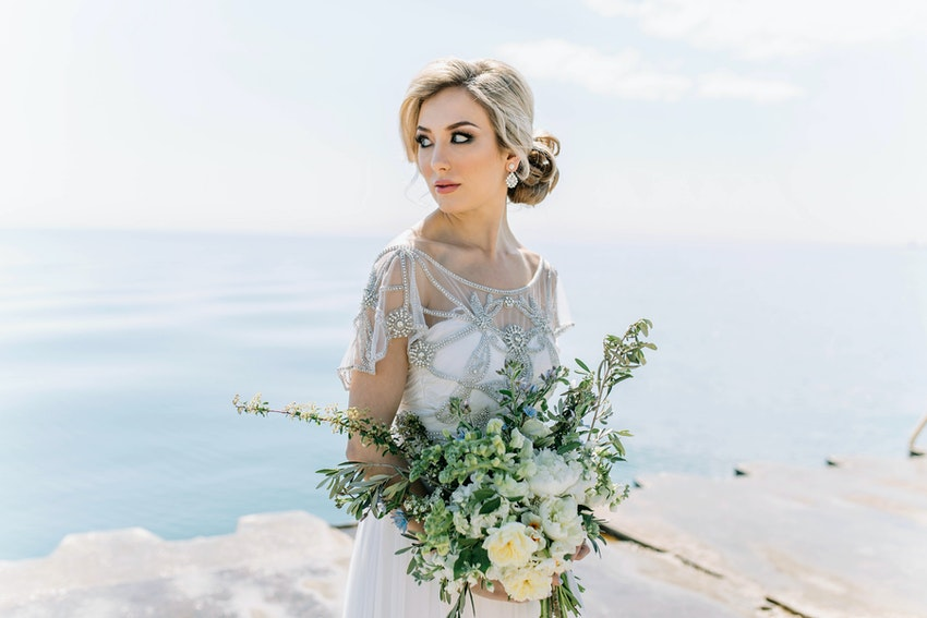 Bride in vintage-inspired dress holding bouquet at lakefront.