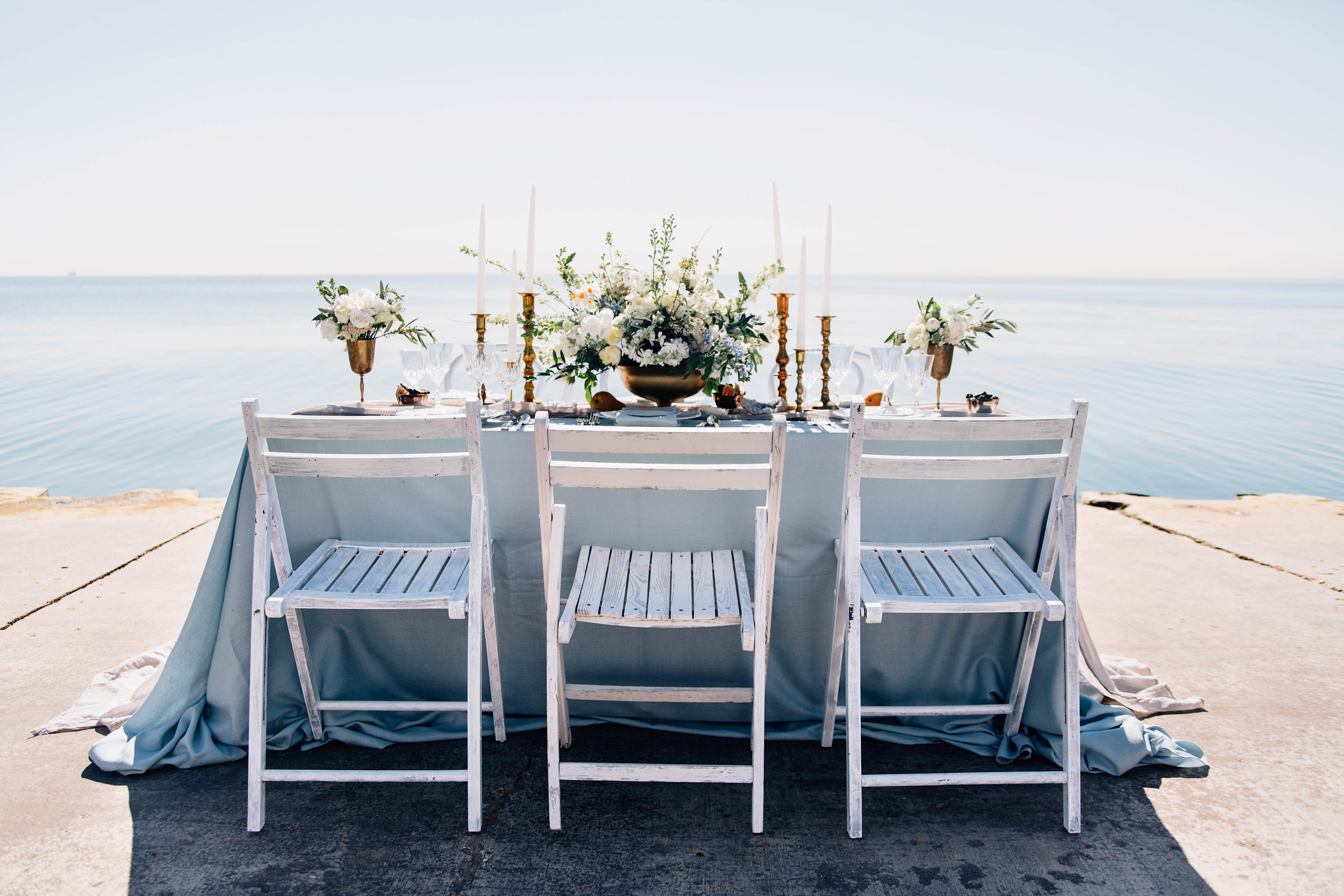 Tablescape with sky blue natural linen, hand-died silk table runner, vintage tabletop elements and distressed white folding chairs with lakefront backdrop.