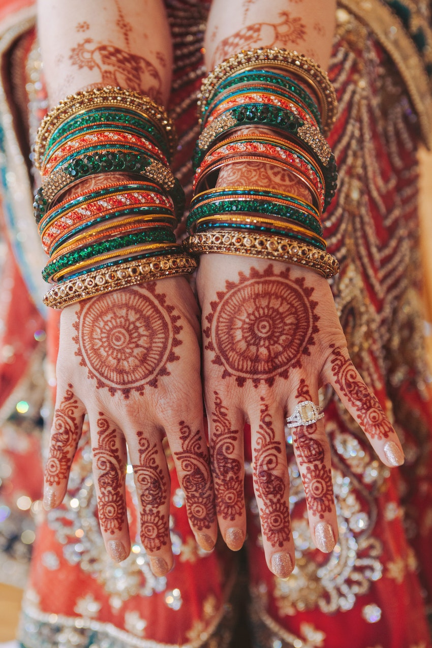 Detail of the bride's jewelry, yellow diamond ring, and Indian Mehndi henna art