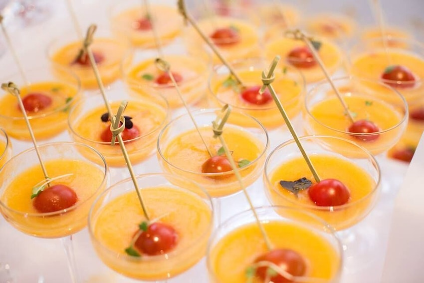 Yellow Tomato Gazpacho Shooter garnished with red micro greens and cherry tomato skewer