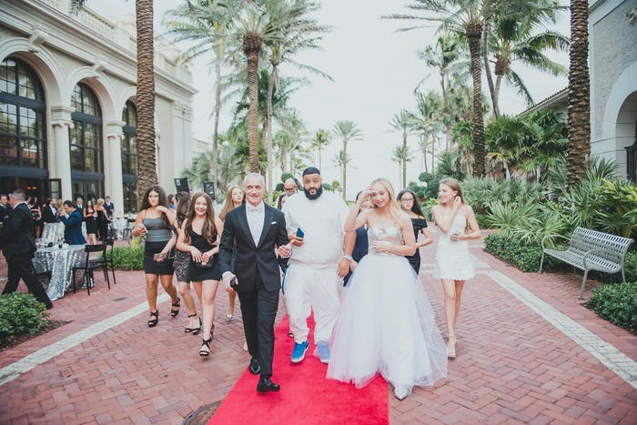 DJ Khaled and a bride walk down a red carpet with people around them