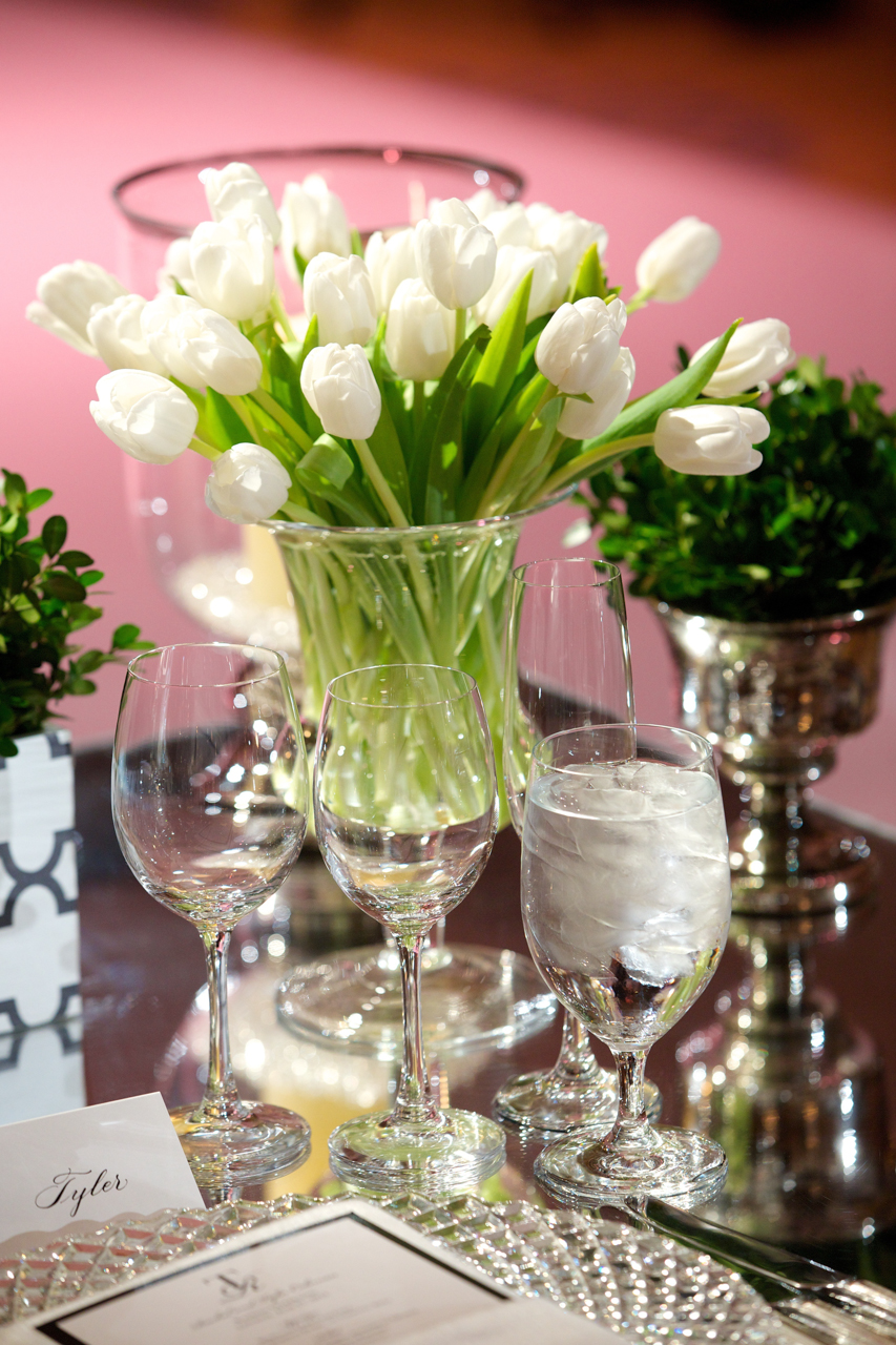 White tulips are used as a centerpiece collection complemented by boxwood leaves in mercury glass vases on top of a mirrored tabletop.