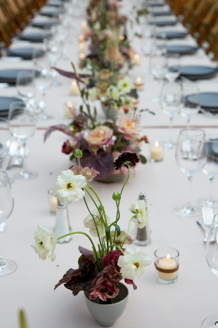 A long rectangular table with branchy floral arrangements dow the center. White table linens and wine glasses are on either sides.