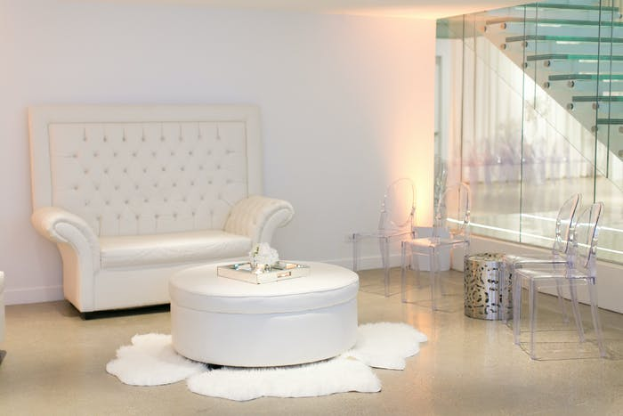 concrete floors with a white quilted love seat and translucent stairs next to it