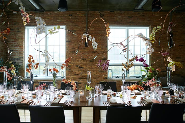 a table in the foreground holds geometric and sparse floral arrangements that extent a few feet into the air. The background holds a brick wall with 2 windows that showcase natural light.
