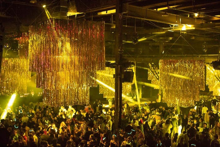 large space with gold tinsel hanging from ceiling. People dance underneath the yellow dance lighting while yellow lazer lights point to the dance floor.