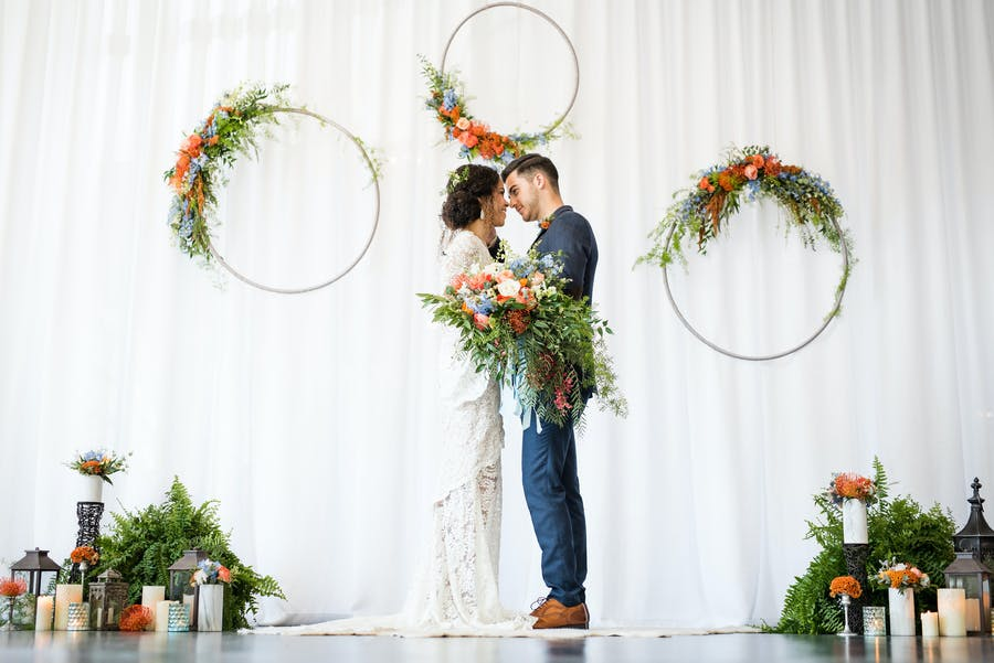 a bride and groom stand embraced in front of a white curtain. Leafy and pink floral arrangements are on rings on the curtain and on the floor at the edges.