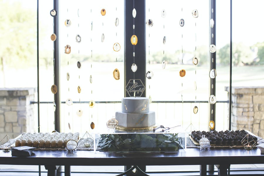 amber beading hangs in front of a window. A dessert table is in the foreground with a two tiered cake and smaller desserts.