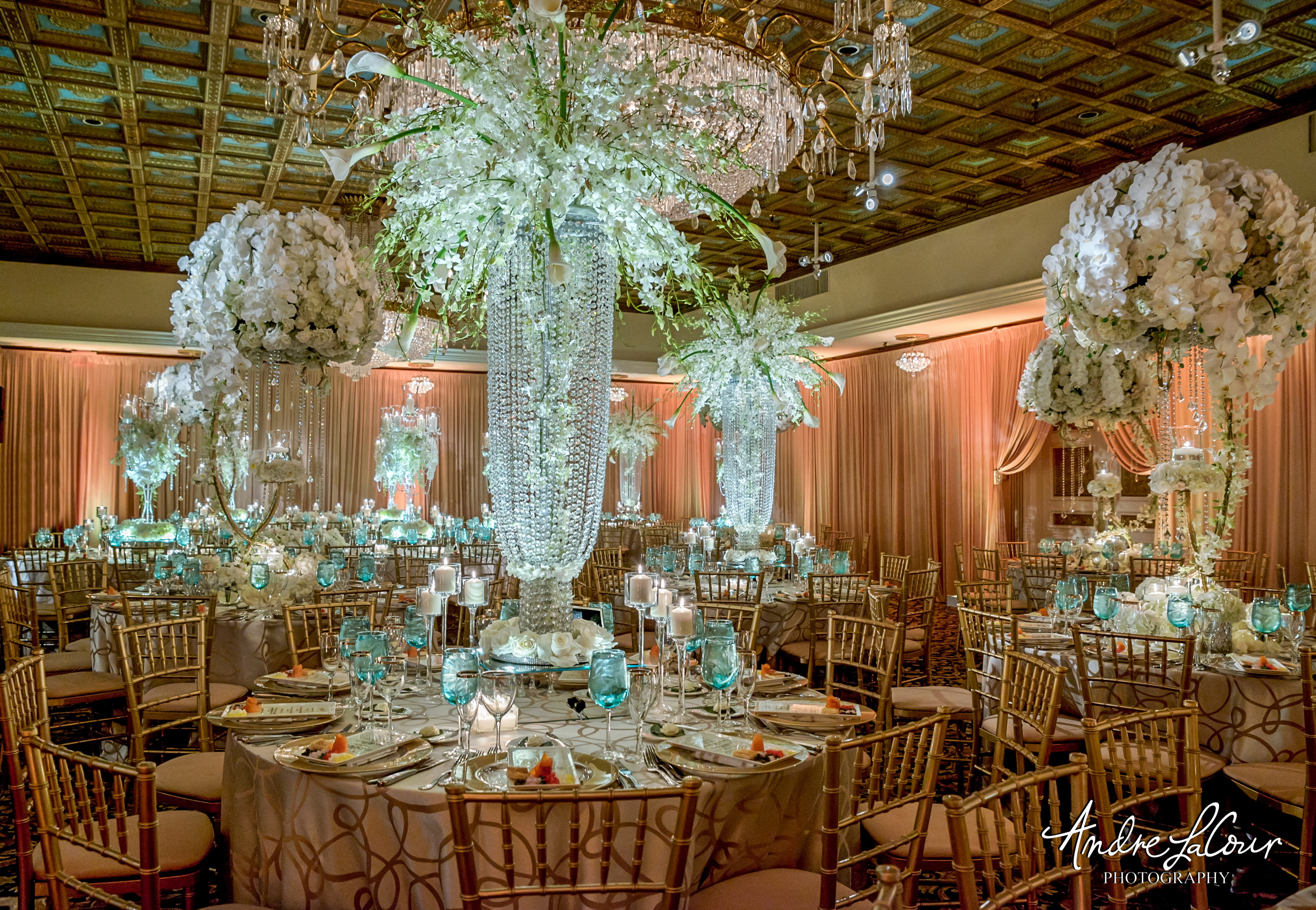 Exquisite wedding reception showcases grand modern centerpieces dressed in crystals and fresh floral.