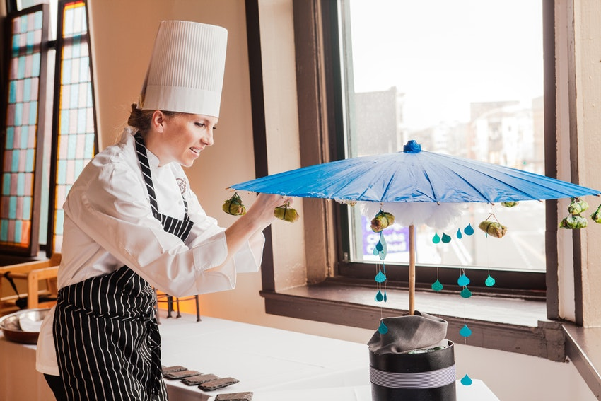 Chef Brittany doing amazing work attaching chicken roll hors d'oeuvres to the parasol, preparing to serve to guest for this baby shower luncheon.