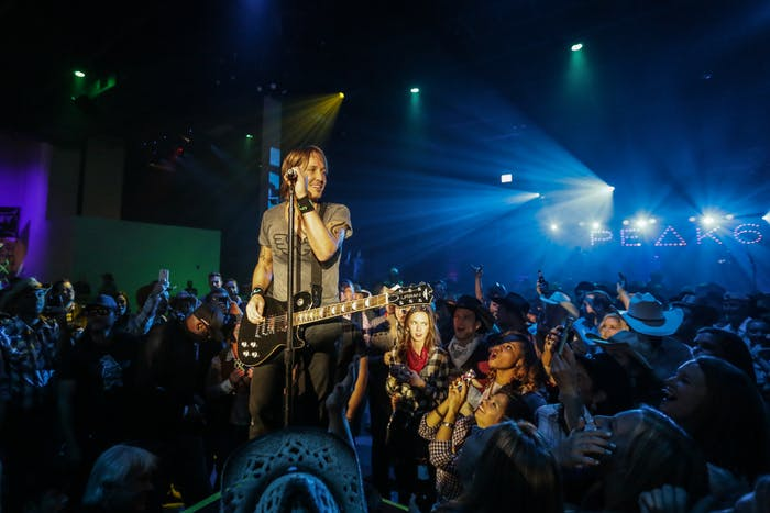 Keith Urban on stage with people around him.