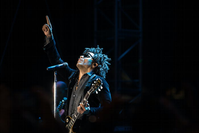 a singer on stage points to the sky while holding his guitar.