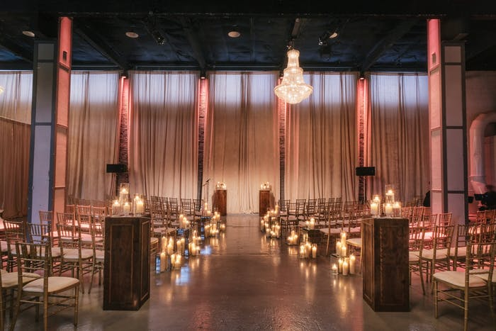 A dimly lit wedding with candles lining the aisle and romantic drapes behind