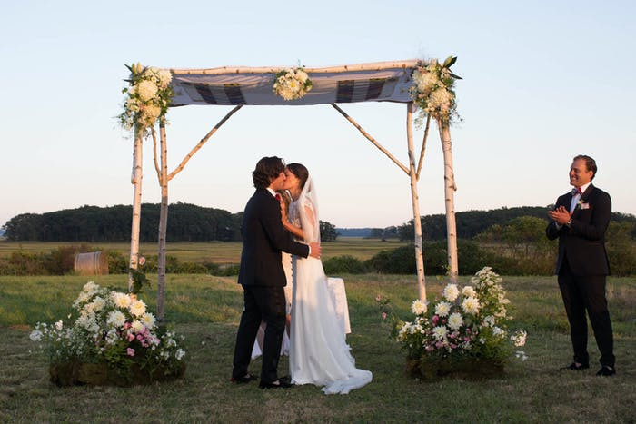 a bride and groom are under their altar with white bouquets on either side and rolling hills in the background.