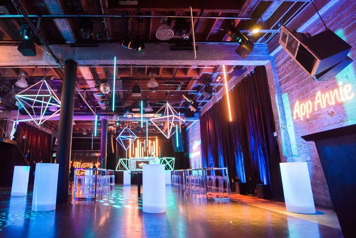 Raw industrial space with neon-geometric installations and neon uplighting.