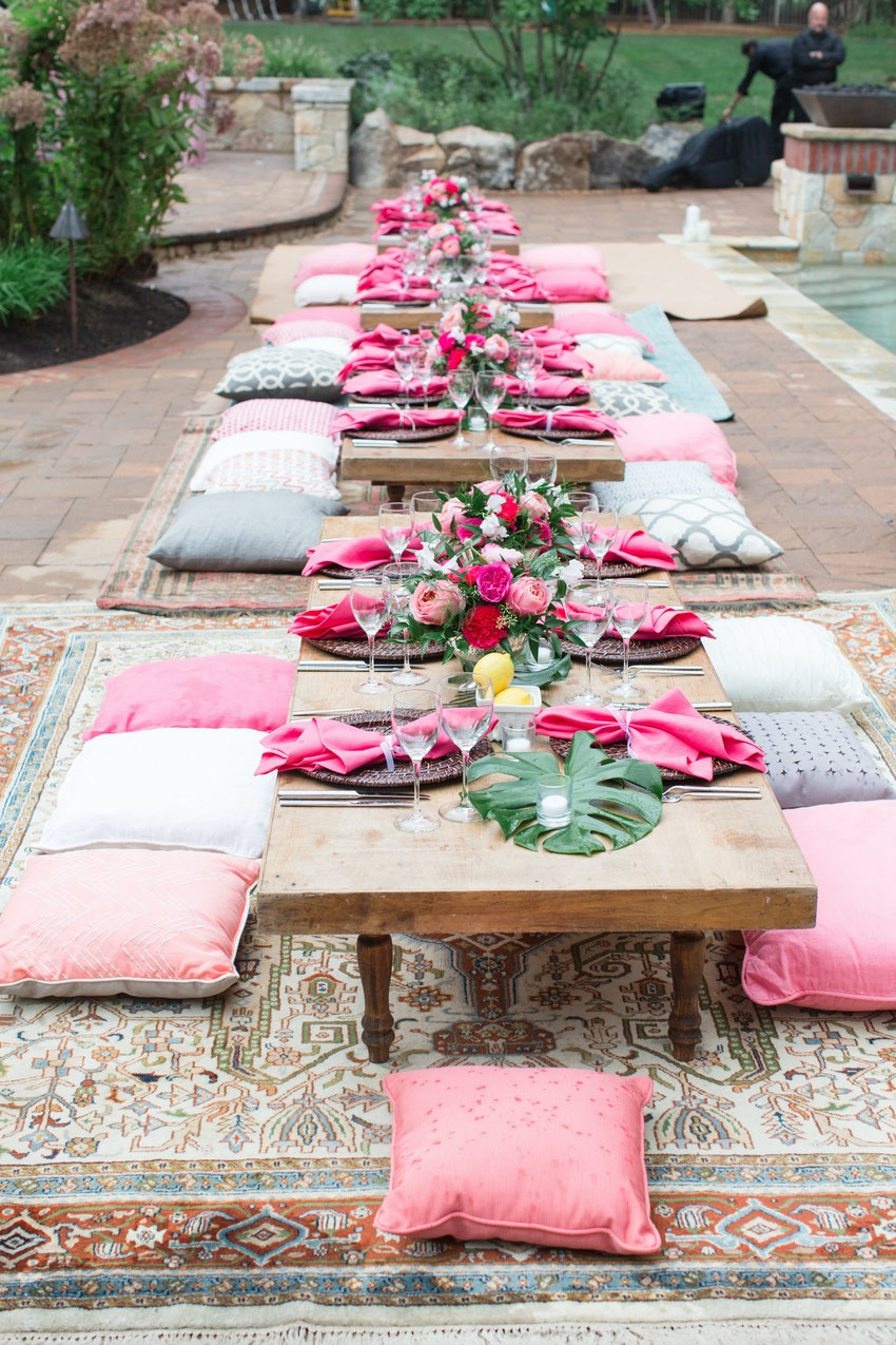 Gorgeous Girl's Night poolside party to celebrate the end of summer featuring specialty rentals of assorted P&J's assorted pillows, rugs and our Flippin low-rise custom built tables.