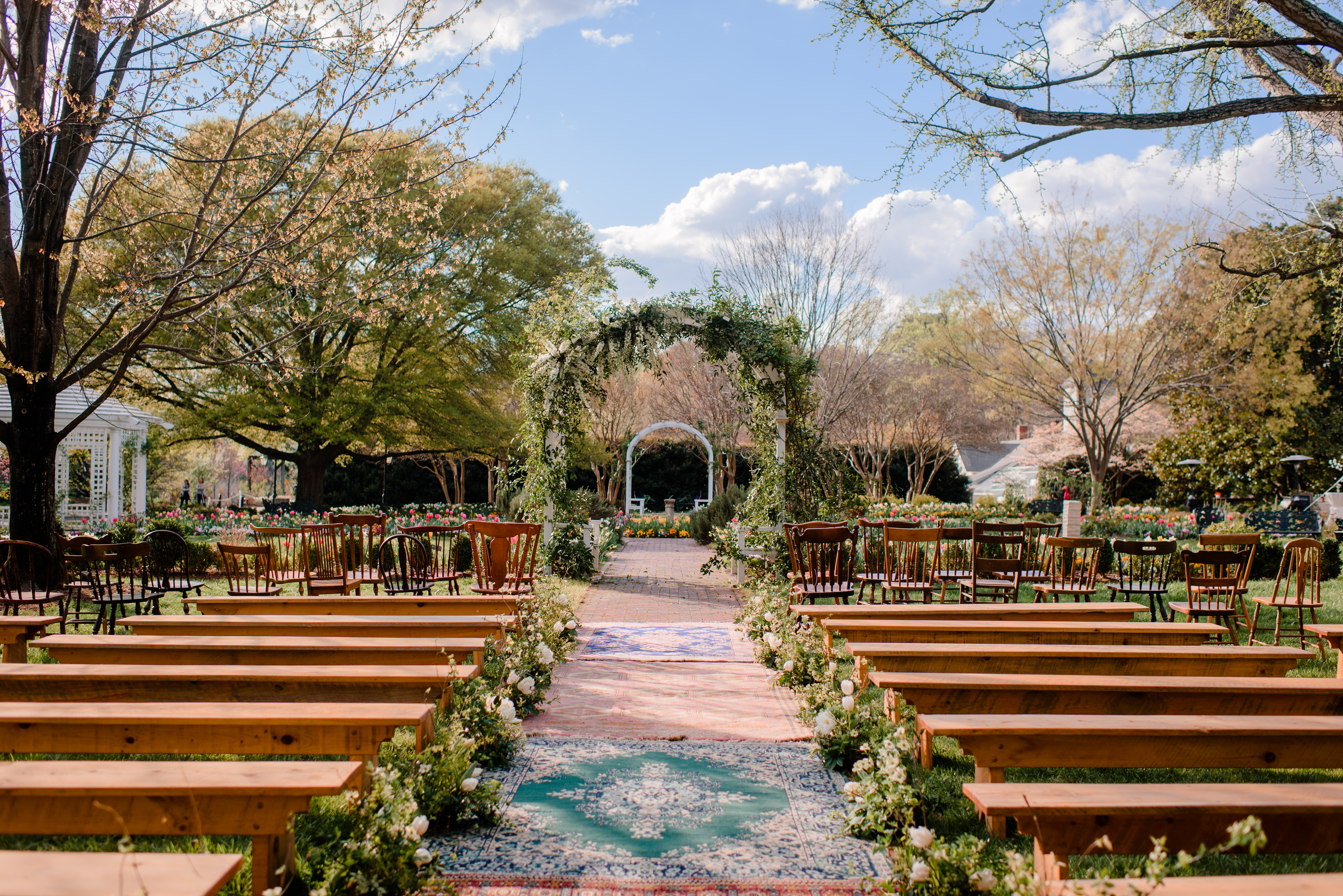 Simply beautiful outdoor wedding ceremony design featuring specialty rentals from Paisley and Jade that include white pine benches, mis-matched vintage wooden chairs and assorted patterned rugs.