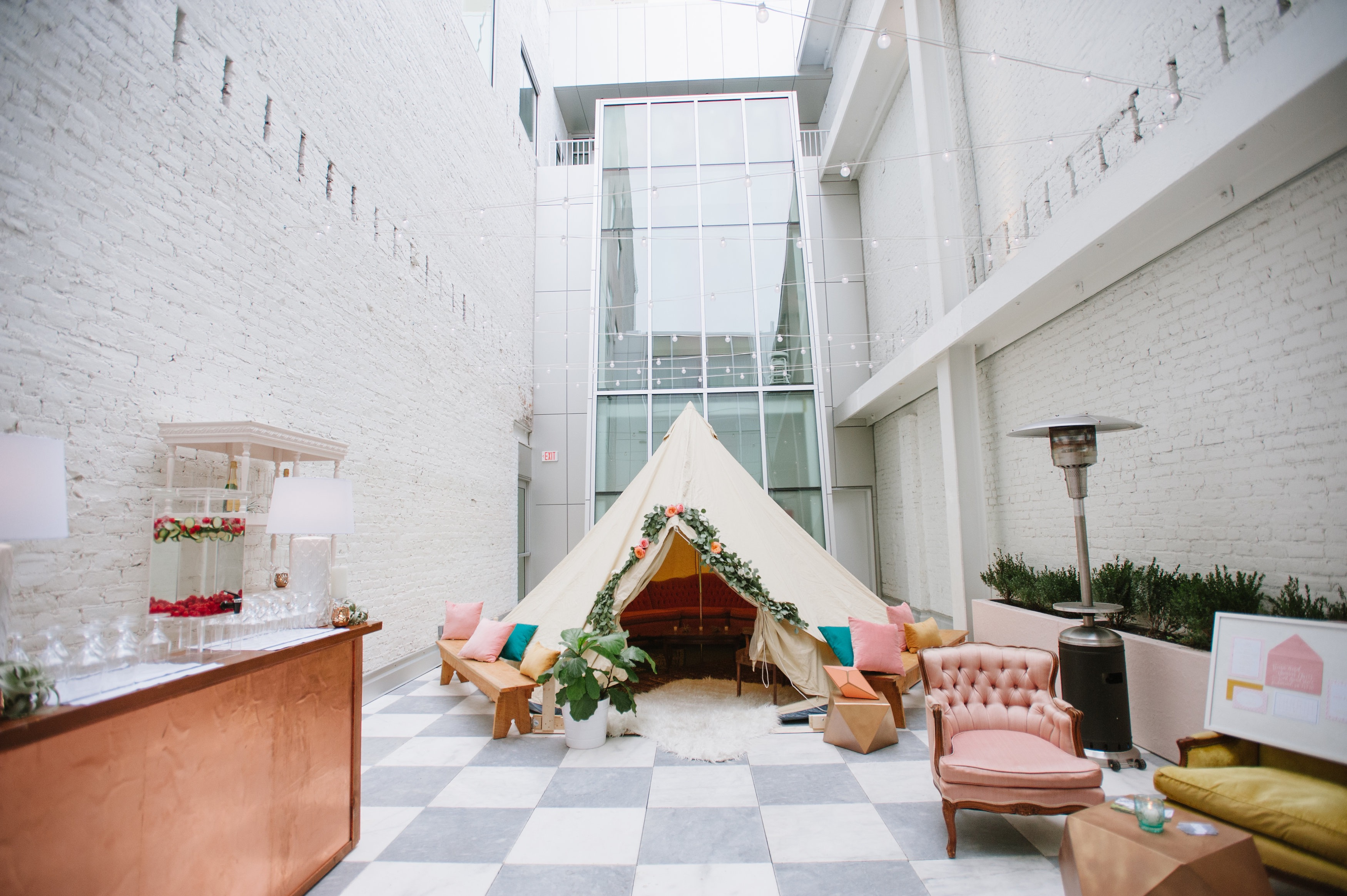 Fun wedding reception inspiration at Quirk Hotel in Richmond, Virginia. Speciality rentals from Paisley and Jade include the canvas tent, vintage lounge, white pine benches, assorted pillows, homestead copper bar and white carved post hutches.