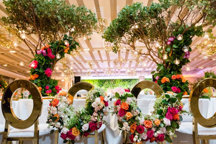 A symmetrical bride and groom table with colorful florals and fairy lights.