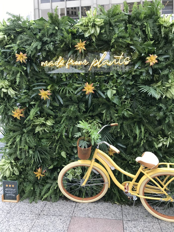 """a yellow vintage bike against a huge green bush. Yellow flowers and a yellow neon sign that says """"made from plants"""" is on the bush."""