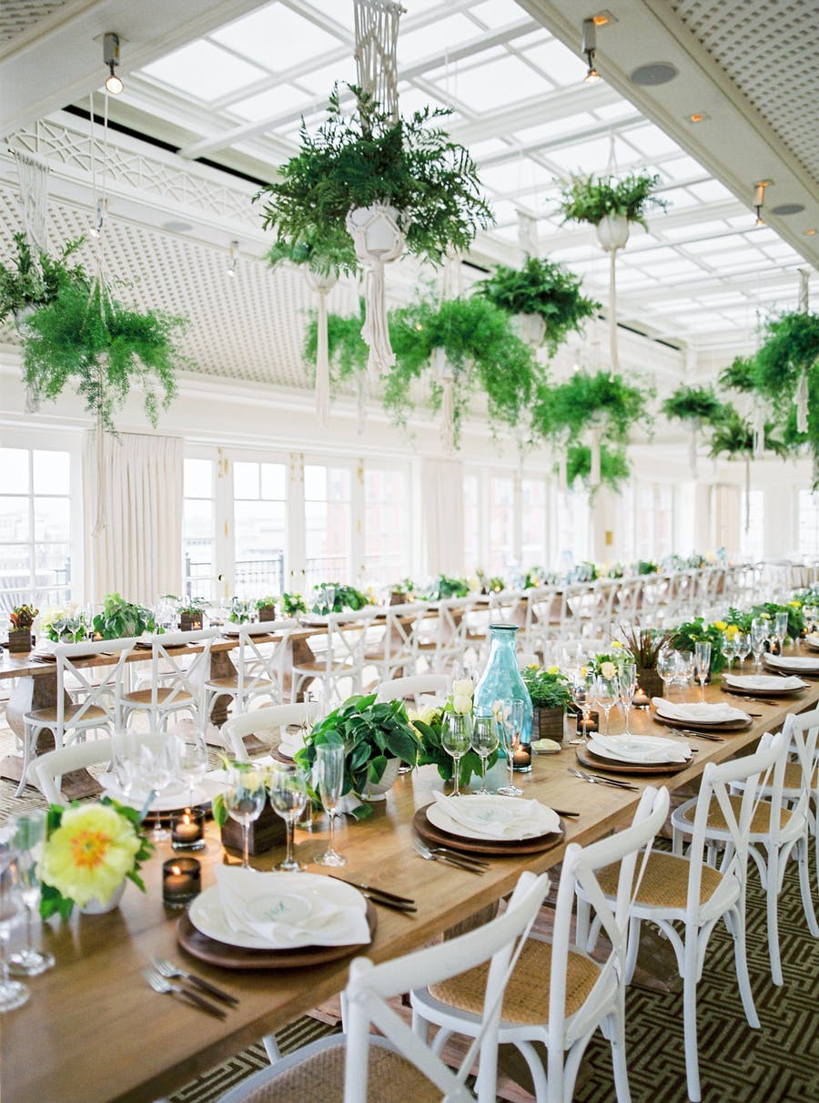 leafy plants hang from the ceiling next to a paned skylight. A wooden table extends through the whole space with white plates and white chairs.