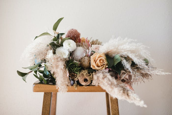A wooden stool holds a feathery and pink bouquet of florals with a cool white backdrop.