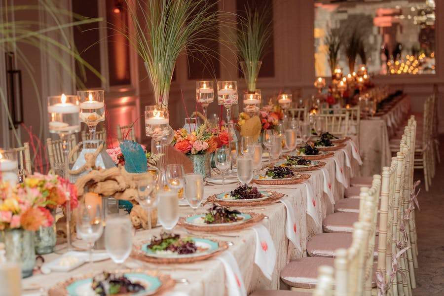 a long table with a white tablecloth and long grass in vases. Tea light candles and pink and orange florals.