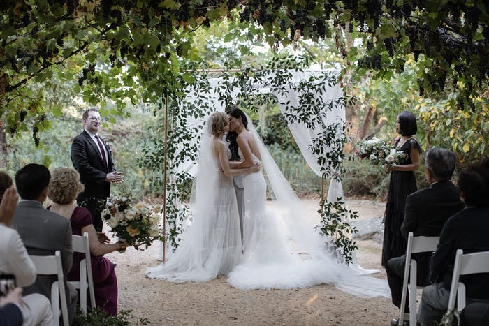 Two brides kiss at the altar with greenery surrounding them.