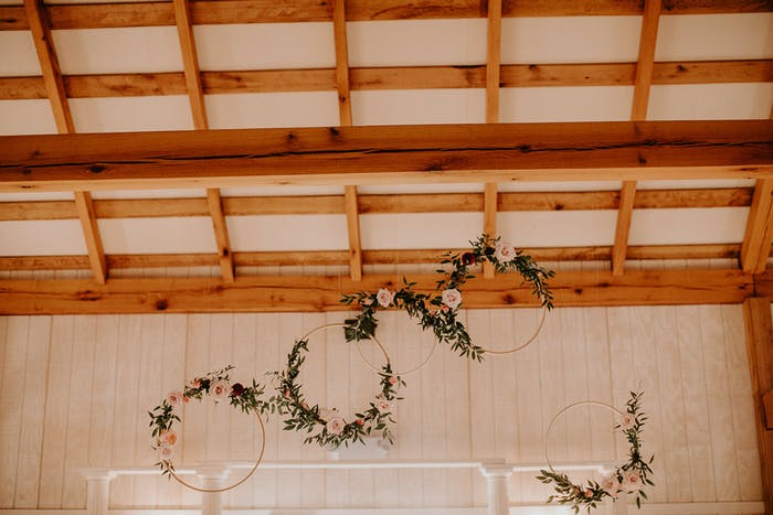 raw wooden accented cieling with hoops of greenery interlocking